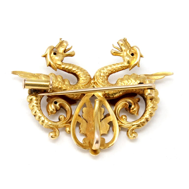 A brooch converting into a pendant featuring two dragons facing each other set in 14k yellow gold, circa 1940.