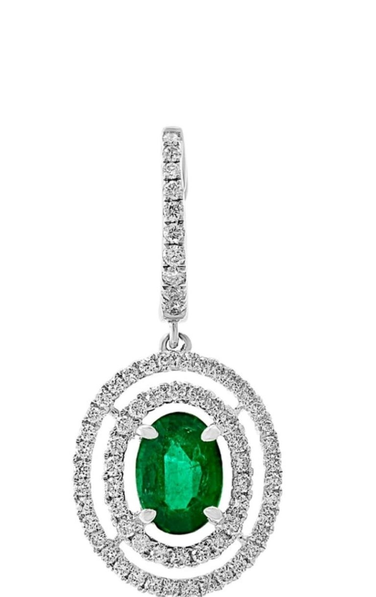 Beautiful 18Kt White gold setting with 1.68 carats of round brilliant cut diamonds encircle the two oval brilliant cut emeralds. The two emeralds combine for 1.05 carats.