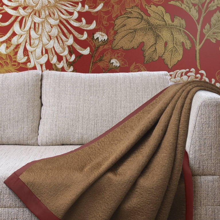 Luxuriously soft, this blanket blends the warmth of 10% virgin wool with the softness of 80% mohair, framed by a contrasting silk border for a richly-tailored finish. This generously sized blanket features an elegant brown and red color combination