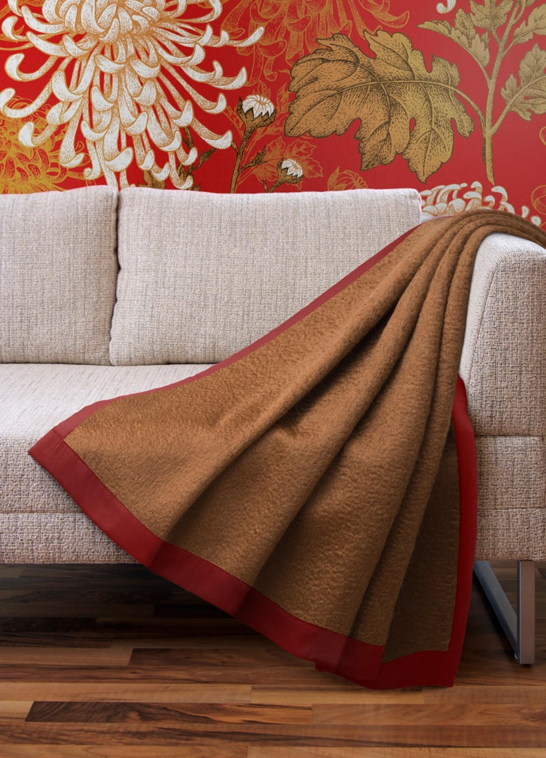 Luxuriously soft, this plaid blends the warmth of 10% virgin wool with the softness of 80% mohair, framed by a contrasting silk border for a richly-tailored finish. This generously sized plaid features an elegant brown and red color combination that