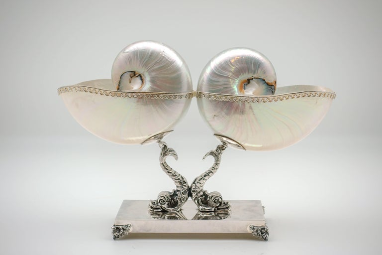 What could be better than a mother-of-pearl Nautilus? Two mother-of-pearl nautilus shells. Edged in a pierced, Italian sterling silver design, they are mounted on a triton base for a pleasing display of natural beauty. Handmade in Rome, Italy.