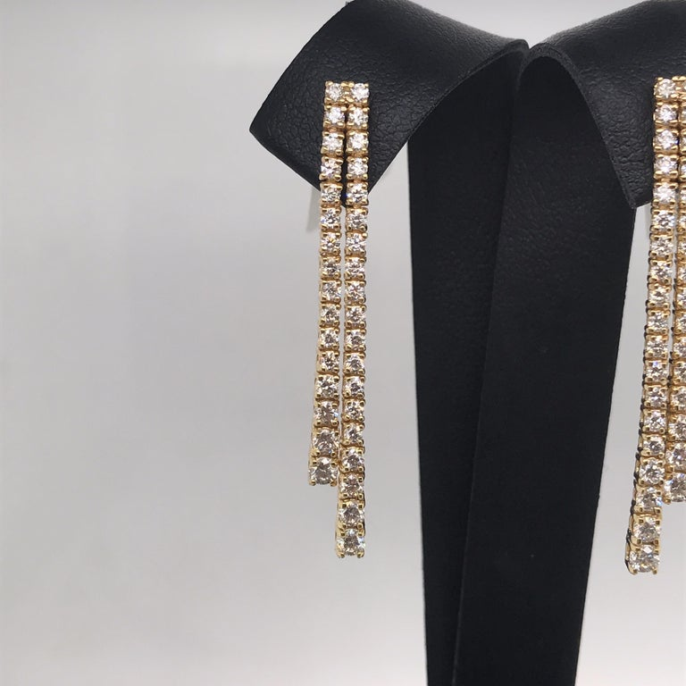 14K Yellow gold drop earrings featuring two diamond rows containing 70 round brilliants weighing 1.52 carats.  Color G Clarity SI2 Available in white gold.