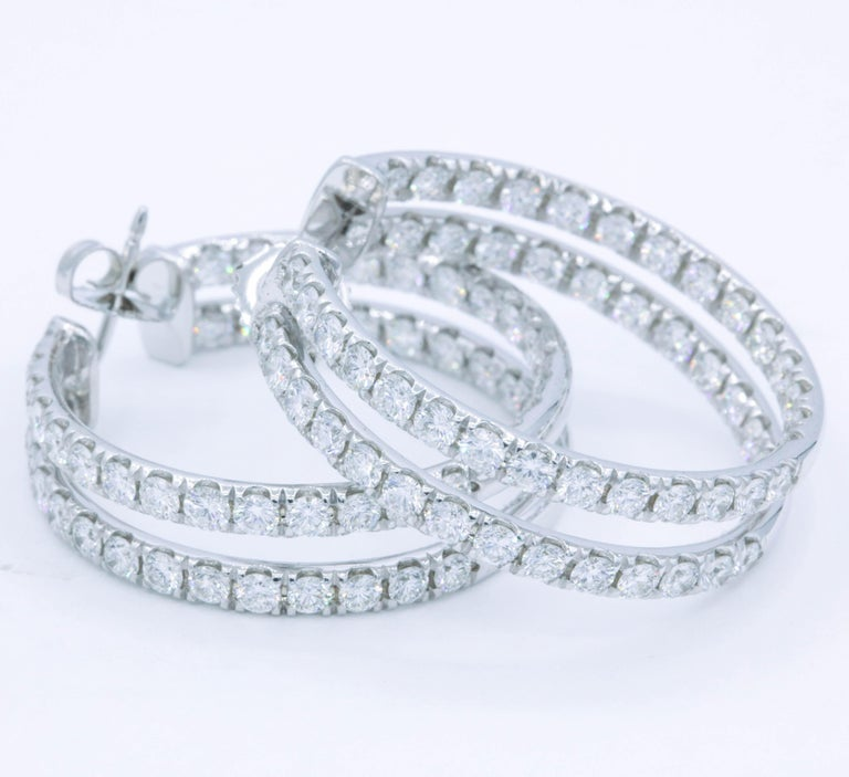 Double row hoop earrings containing 112 round brilliants, weighing 5.60 carats, in 14k white gold.  Color: G-H Clarity: SI