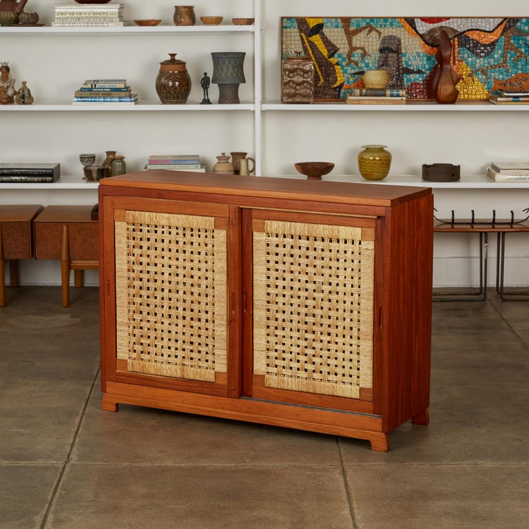 Bauhaus-trained, Mexico City-based Michael van Beuren created highly functional modern design inspired by Mexican vernacular styles and materials. This example is a compact solid mahogany credenza with double sliding doors on either side. The four