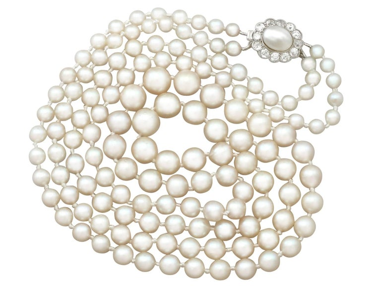 A fine and impressive vintage double strand cultured pearl necklace with an antique 0.84 carat diamond and natural pearl, 14 karat yellow gold, platinum set clasp; part of our diverse pearl jewelry collection  This impressive vintage double strand