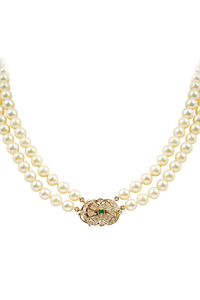 A classic double strand pearl necklace. Composed of two strands of well matched cream colored cultured pearls and completed by a 14 karat yellow gold and diamond clasp highlighting a square shaped emerald of approximately 0.30 carat. Total diamond