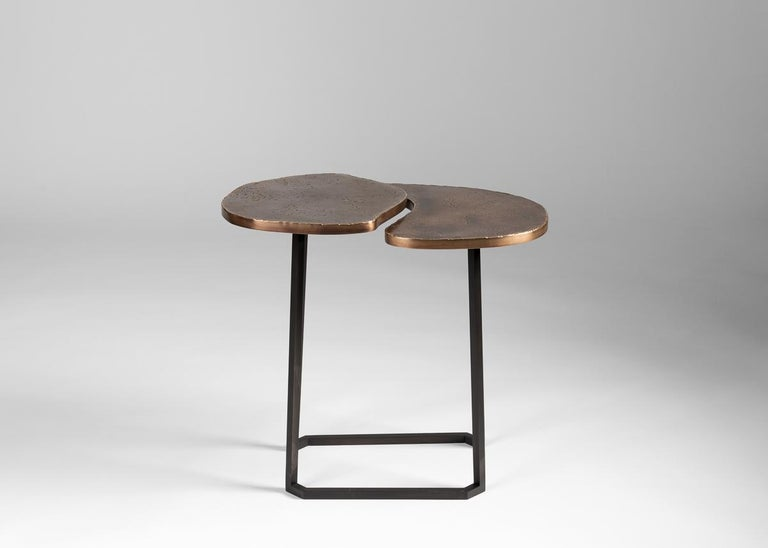 This set of conjoining tables, topped in dappled brass and supported by blackened steel legs, is not just a work of supreme craftsmanship, but of stunning elegance, its two surfaces separated by a subtle gap that gives them an unexpected