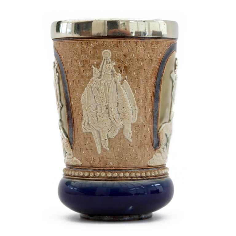 A very rare Doulton Lambeth art pottery Huntsman beaker decorated with figures of huntsmen by renowned artist Minnie Thompson and assisted by Matilda Martyn and Mary Lilly. The stoneware beaker dated 1882 is decorated with three panels each moulded