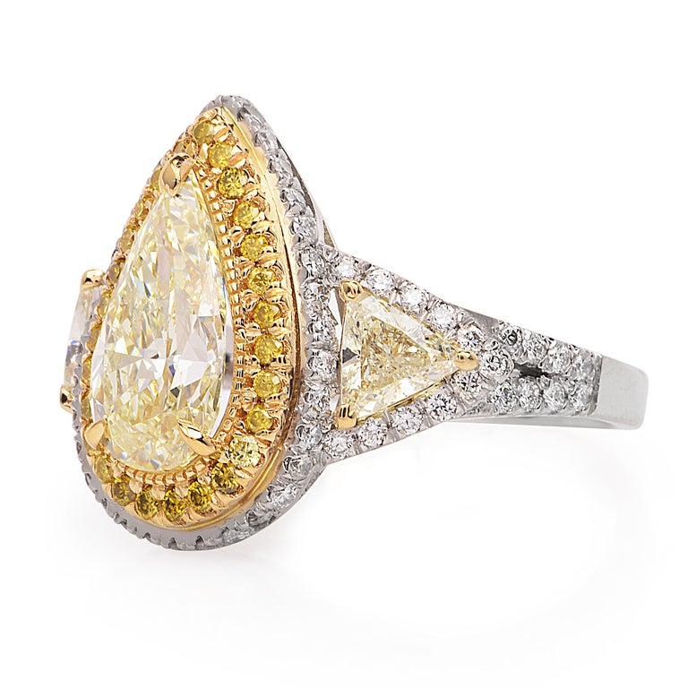 This vintage inspired Engagement Ring crafted in luxurious Platinum and 18k yellow .  Adorning the center is one pear shaped   Fancy yellow pear shaped diamond weighing approx. 2.39 carats.   This yellow diamond is of VS2-SI1 clarity with even color