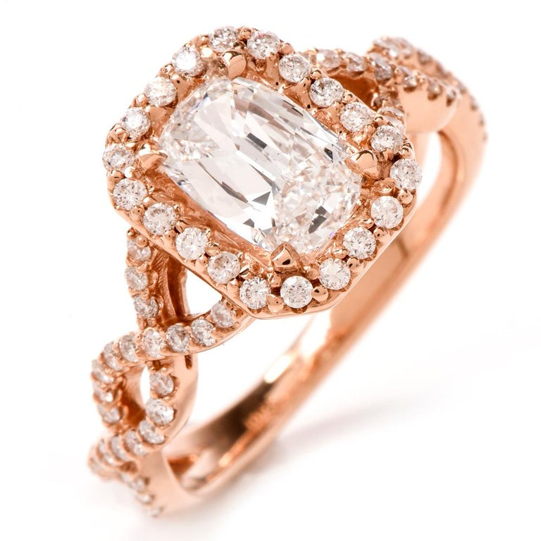 This stunning  Diamond ring is crafted in 18K rose gold. Displaying a prominent four prong set emerald cut diamond approx. 1.01 CT, D color, VS1 clarity. Surrounded by a halo of pave set round-cut diamonds, further embellished along a twisted shank