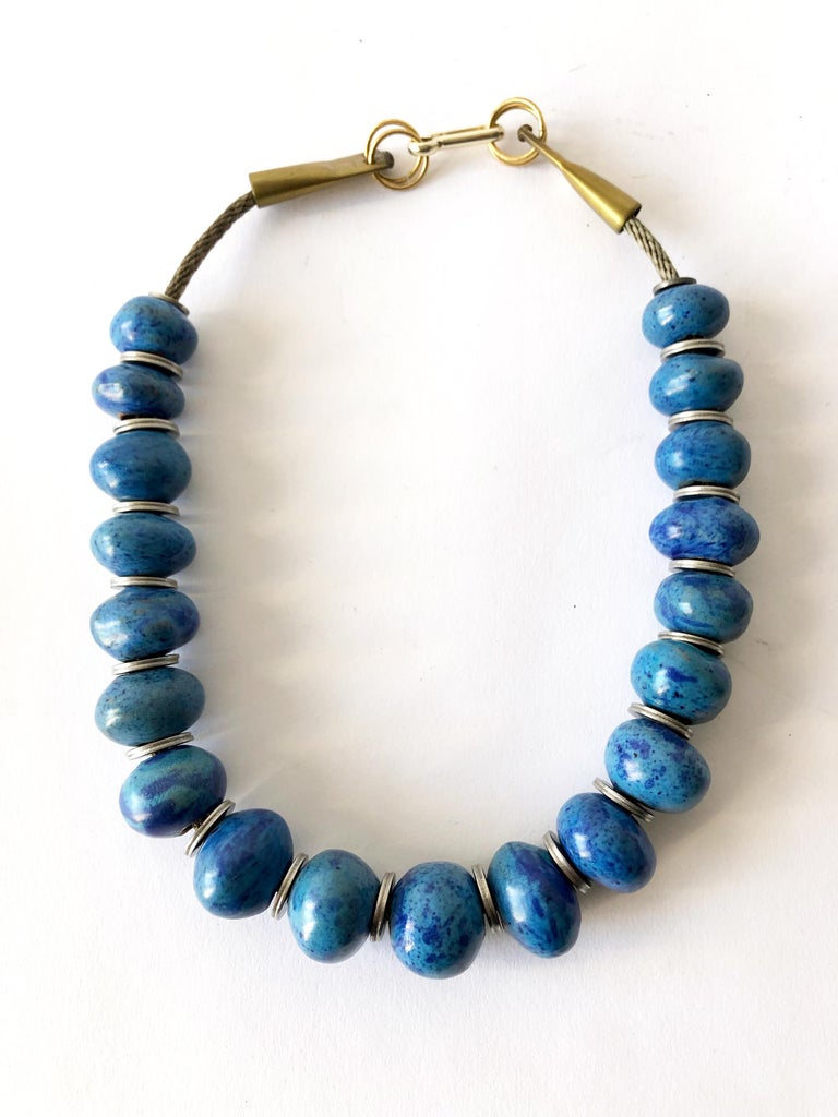 Handmade necklace of nineteen ovoid mottled turquoise beads separated by steel washers and strung on cable wire created by Doyle Lane of Los Angeles, California.  Necklace measures 22