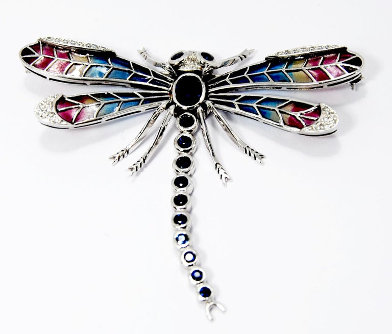 An exquisite an art nouveau style  dragonfly brooch, with multicolored plique à jour  wings, with oval sapphire set in the centre, weighing an estimated 3.00ct, and 12 round saphphires in eyes and body totalling 16ct of sahhpires, wings are