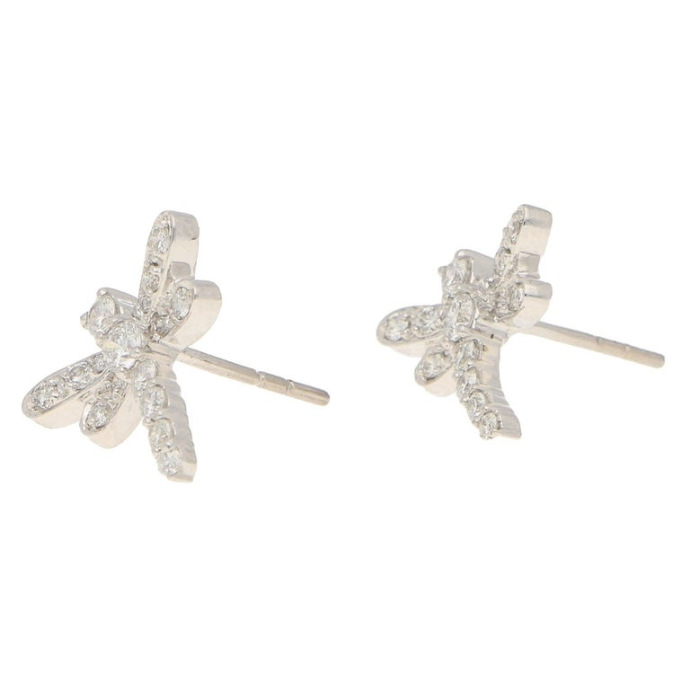 A pair of dragonfly diamond stud earrings in 18-karat white gold. Each earring is designed as a dragonfly in flight, claw- and grain-set throughout with round brilliant-cut diamonds. The earrings are secured to reverse with a post and butterfly