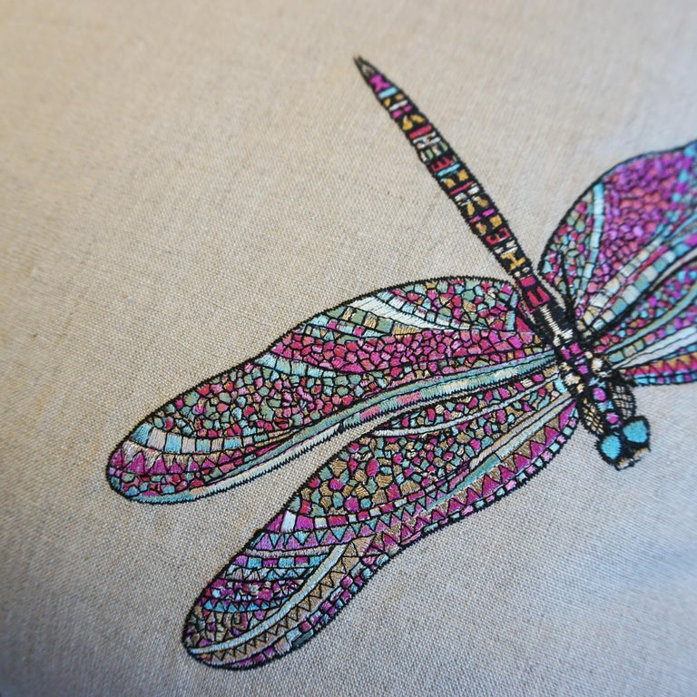 Our Dancing Dragonfly pillows are one of a kind. The pillows are made with a stunning embroidered linen print of multicolored dragonflies. The back it sewn in a distressed textured fabric and is bordered with a pink piping accent.
