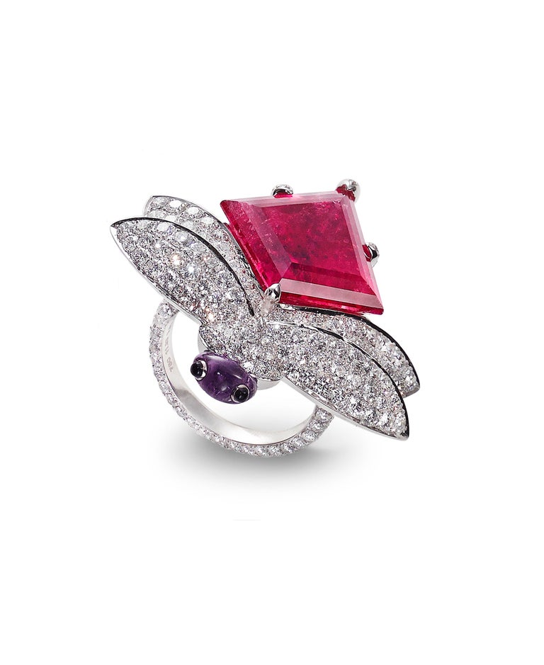 This fun cocktail ring features a Dragonfly motif with a  Kite Shaped Rubellite Tourmaline, weighing 11.93 carats, accented with white Diamond pave wings totaling 4.80 carats, Amethyst, and Onyx Face and Eyes, hand-crafted in 18 karat white