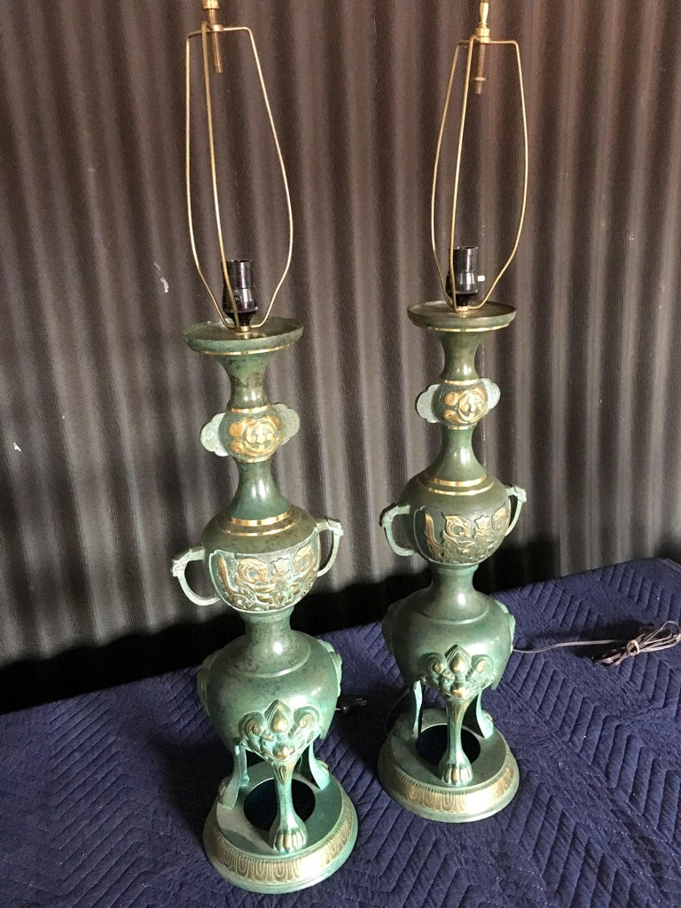 In the style of James Mont, these amazing lamps are just perfect! Bronze lamps trimmed in brass. Simply gorgeous! Lamps are in excellent condition with no visible signs of wear. Wiring is perfect and the lamps are ready to use right