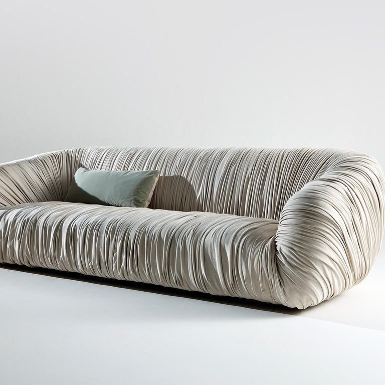 This stunning three-seat from the Drapè collection combines unique design, exquisite craftsmanship, and extra comfort. The metal structure is linear and yet welcoming, thanks to the curved back and armrests covered by thick padding. The distinctive