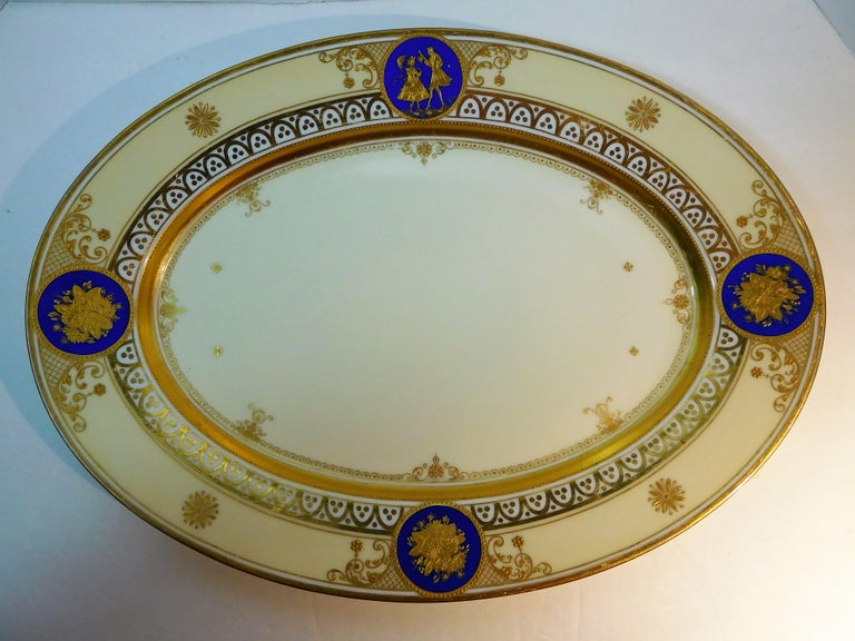 This German fine porcelain large oval platter is from the Dresden atelier of Ambrosius Lamm (active 1887-1934), and was hand painted in enamels and hand-burnished with double-gold incrustation in his studio. It is signed on the bottom with his logo,