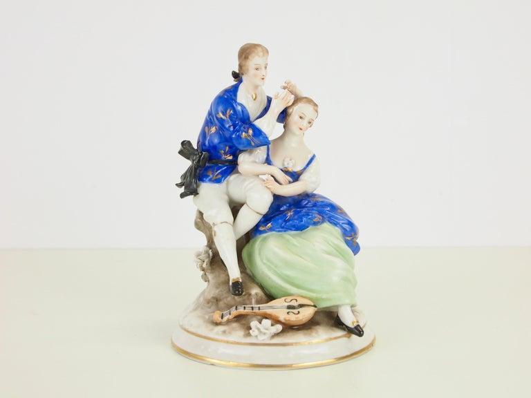 An antique/midcentury fine porcelain hand painted statuette depicting a romantic Classic couple.  Lovely high quality fine porcelain statuette made by the Saxon Porzellan manufacturer Ackermann & Fritze. It has very fine hand painted details and