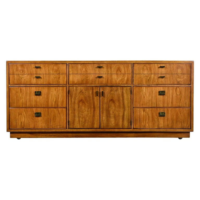 Dorothy Draper style Campaign dresser made by esteemed US furniture maker Drexel Heritage, circa 1970s. Old growth flaxen flared grain pecan top to bottom. Brass pull hardware ties together British traditional and Eastern design. This dresser
