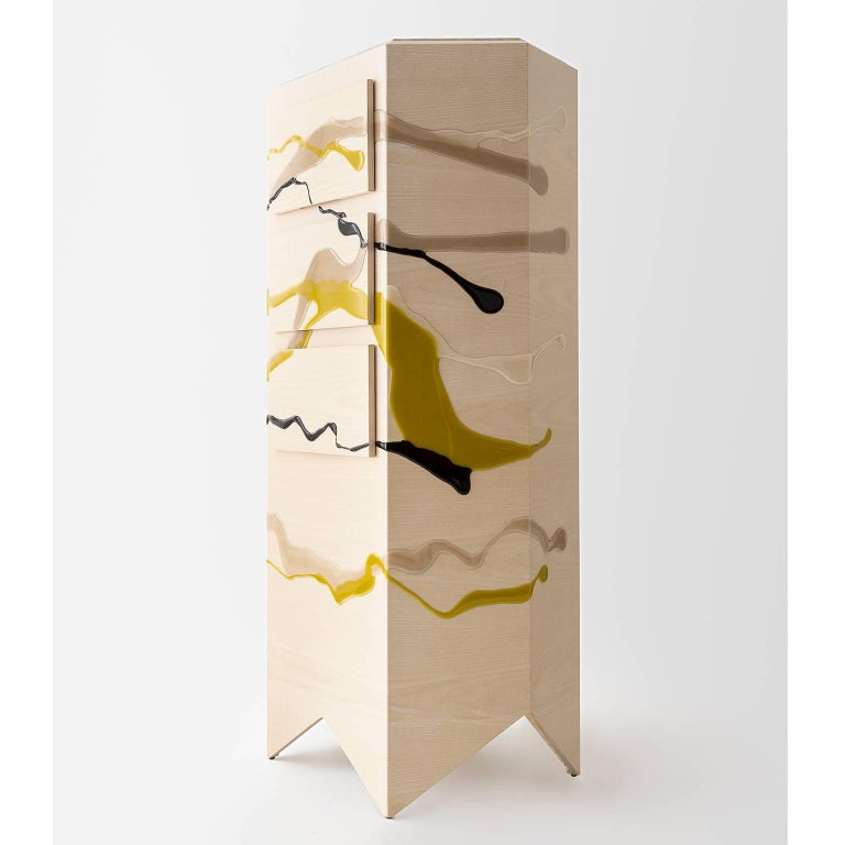 This Drip/Fold Dresser by Noble Goods is constructed of a single sheet of ash plywood that has been hand-dripped with liquid resin, then bent into a hexagonal shape. This piece is finished with a quartzite top, a unique and natural stone.   Its