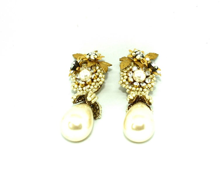 Amazing drop faux pearl clips earrings by former Miriam Haskell designer Larry Vrba. These stunning clip earrings are extremely detailed, adorned with clusters of faux pearls and white diamante stones in a floral theme, ending with a large
