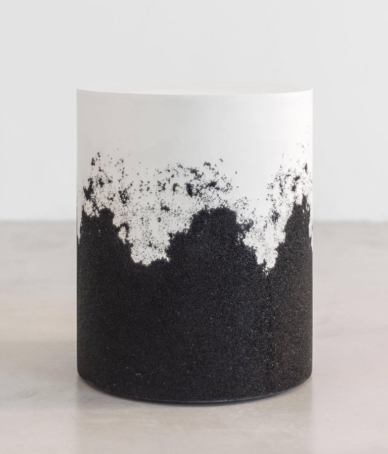 A layering of cement and crushed aggregates, the made-to-order drum consists of an hand-dyed white cement top and a packed black silica bottom. Poured by hand over the jagged minerals, the white cement merges the materials to create a unique organic