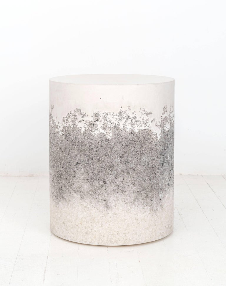 A layering of cement and crushed aggregates, the made-to-order drum consists of a hand-dyed white cement top and a packed white rock salt center and grey rock salt bottom. Poured by hand over the jagged granules, the white cement combines the