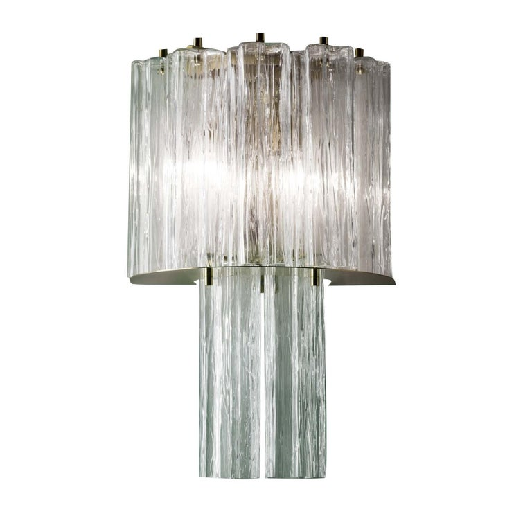 Part of the Home Couture collection, this super sconce is a splendid interpretation of Art Deco glamour. Its structure in metal with a brass finish creates two layers of diffusers in glass that create the effect of a precious jewel mounted on the