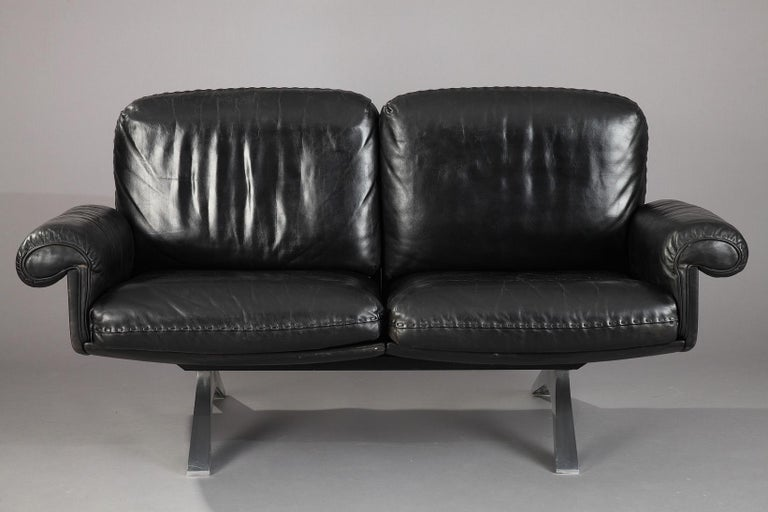 Retro De Sede DS 31 living room set composed of a two-seat sofa and a swivel lounge armchair with its ottoman. Manufactured in the 1970s by De Sede craftsman from Switzerland, these pieces are in soft black leather upholstery, with chrome-plated