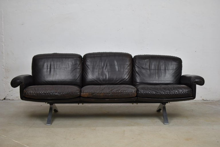 DS31 three-seat by De Sede, Switzerland 1970s. Stunning dark brown aniline leather with whipstitch edge detail standing on a brushed aluminium swivel base. Extremely comfortable and in good vintage condition (some visible wear on the back of the
