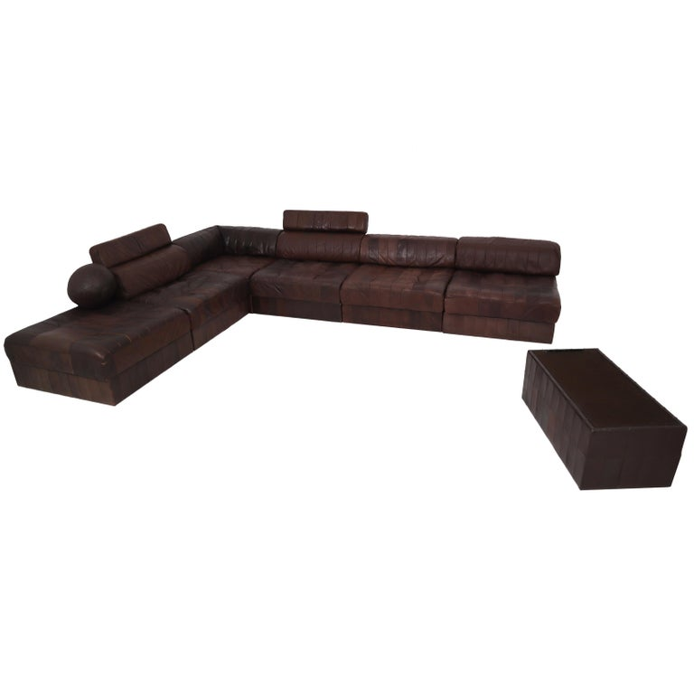 We are delighted to bring to you an original and extremely desirable De Sede DS 88 sectional sofa in patchwork brown-cognac aniline leather with bolster cushions. Hand built in the 1970s to incredibly high standards by De Sede craftsman in