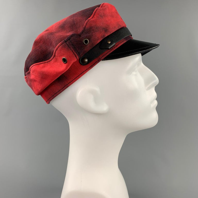 DSQUARED2 hat comes in a red & black cotton with a leather brim featuring a biker style. Made in Italy.  New With Tags.  Marked: S Original Retail Price: $568.00  Measurements:  Opening: 1 in. Brim: 2 in. Height: 3 in.