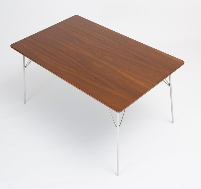 """A rectangular dining table with walnut veneered surface and folding metal legs, designed by Ray and Charles Eames and produced by Herman Miller. Dubbed the DTM-10 (""""Dining Table Metal""""), this example was part of a series of tables introduced in 1947"""