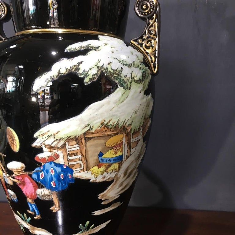 Dudson black glaze vase with small twin scroll handles, elaborately decorated with bright raised enamel chinoiserie scenes. Rare printed mark 'EUTERPE', circa 1875.