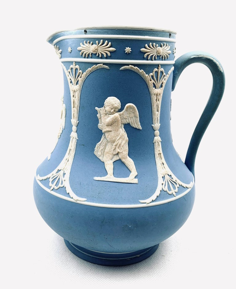 Dudson neoclassical pitcher in blue Jasperware. Decorated with sprig molded accents and cherub scenes. The interior is glazed. There is wear to the handle with some loss of color. The pewter top is missing. There are two impressed marks on the