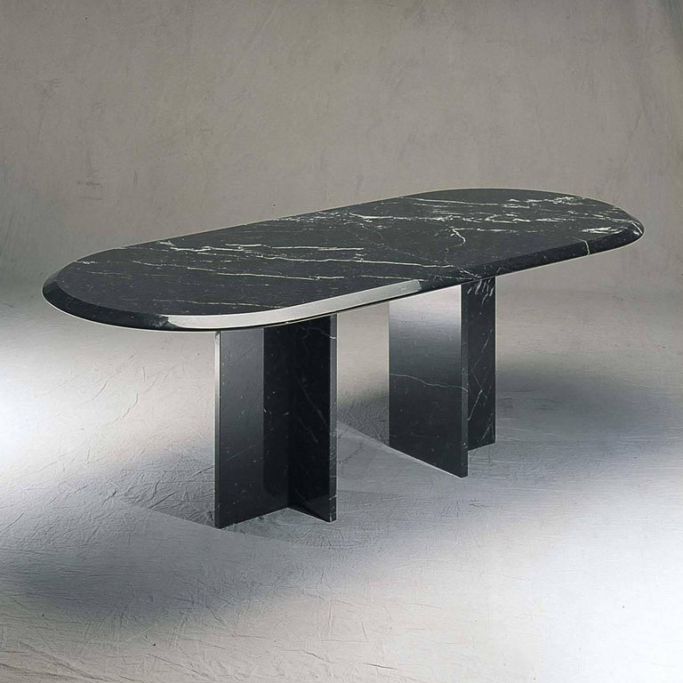 Designed by Achille Castiglioni in 1990, the simple and essential geometry of this table combined with the precious marble create a stunning visual impact. Made entirely of black Marquinia, the elliptical bevel edged top is supported by two T-shaped