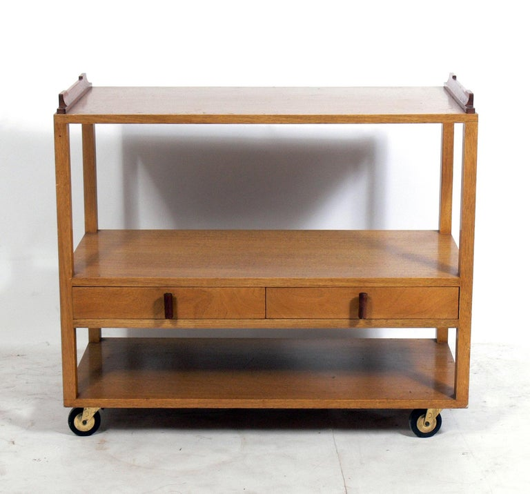 Clean lined bar or serving cart, designed by Edward Wormley for Dunbar, American, circa 1950s. This piece is currently being refinished and can be completed in your choice of color. The price noted includes refinishing in your choice of color. It is
