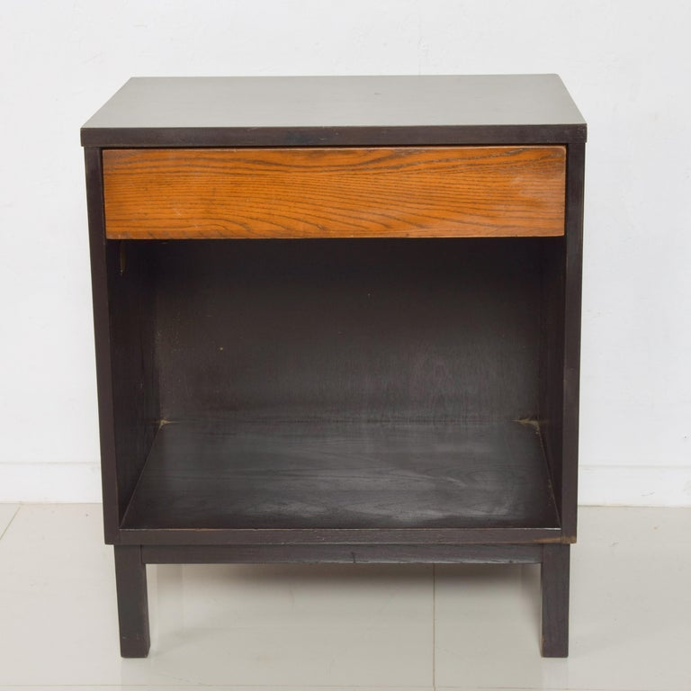 Simple modernism by Dunbar single drawer side table or nightstand pair with open storage area 1960s Handcrafted in two-toned dark ebonized wood and honey toned oak. Maker Gold D Tag label present. DUNBAR Berne Indiana Measures: 25 1/4