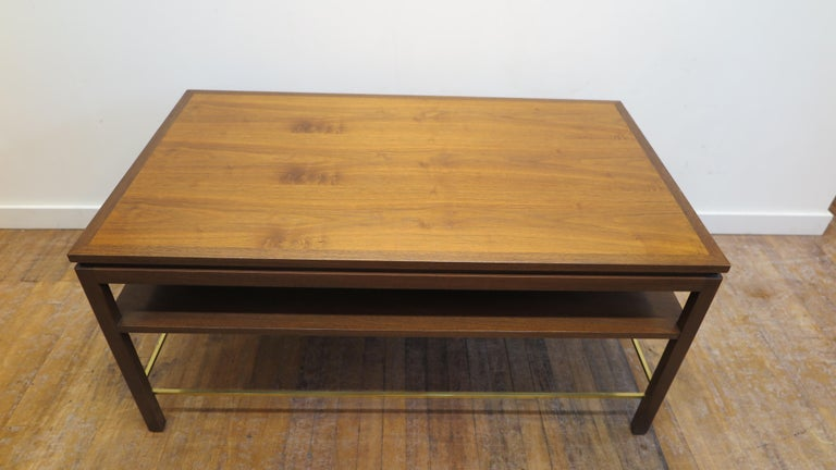 Dunbar cocktail table designed by Edward Wormley for Dunbar. Coffee table in two tone walnut with lower shelf and brass stretcher. Very good original condition. 