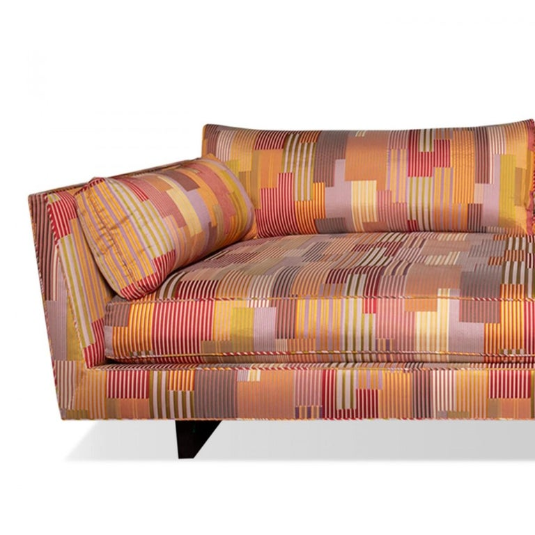 A daybed style sofa by Edward Wormley for Dunbar. USA, circa 1950 with newer material. Upholstered in a stark carpet textile with a multi-color striped and patchwork woven fabric on a dark mahogany base.