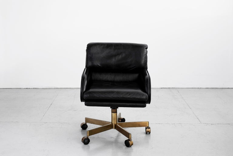 Dunbar executive office chair in original black leather with curved arms and antique brass base on rolling casters. Plush back cushions make it extremely comfortable.