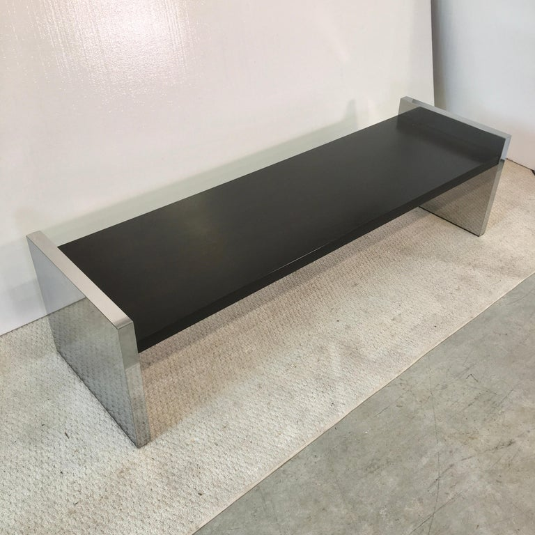 This is the 60 inch long version of this bench (or table) designed by Roger Sprunger for Dunbar circa 1970. Ebonized solid oak between two mirror polished stainless steel clad slab sides. Dunbar metal tag on underside Hand polished and ready to
