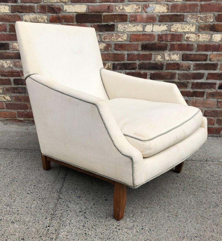 High back lounge chair with crisply tailored angled seat on sculpted walnut legs, circa 1950s. Unsigned but attributed to Dunbar Furniture.