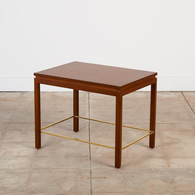 A nearly square side table designed by Edward Wormley for Dunbar. The model 310 has four square post legs that sit flush with the corners of the piece. Each leg is notched to fit a brass stretcher that defines the interior edges of the table. The