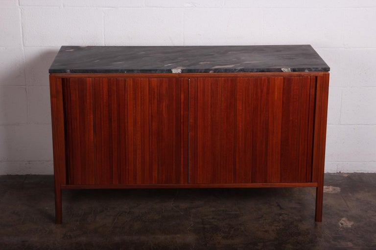 A walnut tambour door bar cabinet with stone top and brass hardware. Designed by Edward Wormley for Dunbar.