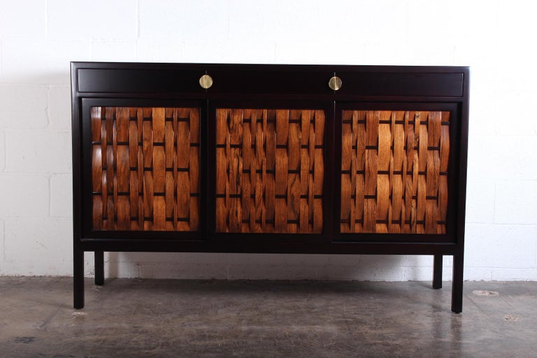A mahogany cabinet with rosewood woven doors and brass hardware designed by Edward Wormley for Dunbar.