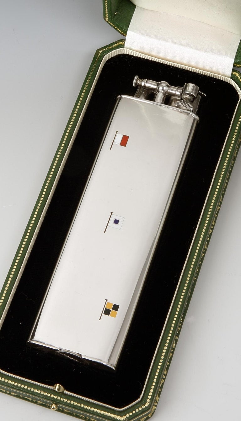 Alfred Dunhill for Cartier, Paris  A sterling silver 'Unique Sports' lighter, the result of a collaboration between Dunhill and Cartier, Paris, the lift arm marked Dunhill, the base marked Cartier, Swiss made, and sterling. The front of the