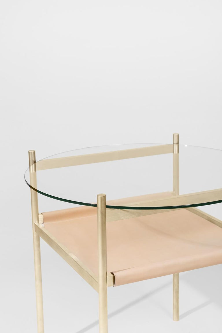 Made to order. Please allow six weeks for production.  Brass frame / clear glass / natural leather sling  The Duotone Furniture series is based on a modular hardware system that pairs sturdy construction with visual lightness and a range of