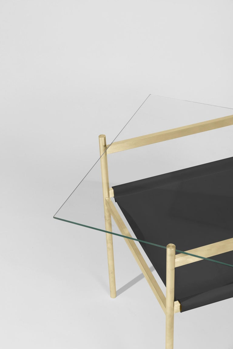 Made to order. Please allow six weeks for production.  Brass Frame / Clear Glass / Black Leather Sling  The Duotone Furniture series is based on a modular hardware system that pairs sturdy construction with visual lightness and a range of